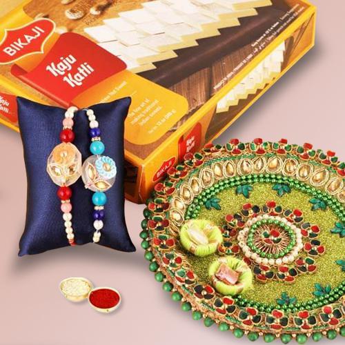 Fantastic Set of 2 Rakhis, Kaju Katli N Puja Thali with Message Card