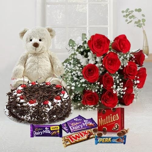 Send 12 Exclusive Dutch Red Roses Bouquet with Cake 1 Lb, Cadburys Assorted Chocolates and a Cute Teddy Bear to india.