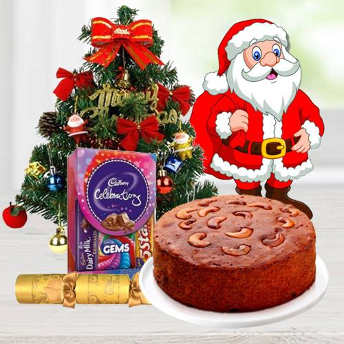 "Christmas Fruit Cake 1 Lbs. with Christmas Tree 1 Ft. long artificial, Assorted Cadbury""s Chocolates for hanging ( 130 G.), Star and Bells for decoration, Santa Claus and  Handheld Ribbon Crackers for Christmas"