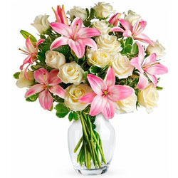 Distinctive display of Pink Lilies N White Roses in Glass Vase
