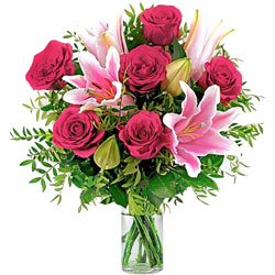 Vibrant display of Red Roses N Pink Lilies in Glass Vase